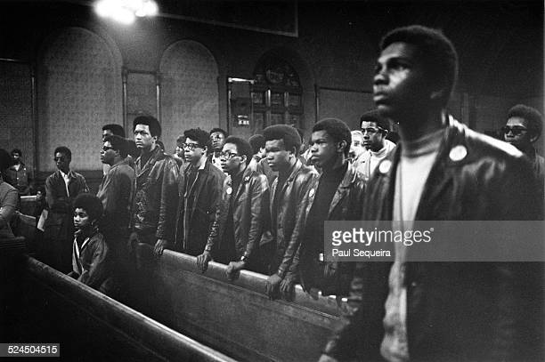A group of young African American men listen to Fred Hampton speaking at the Church of the Epiphany or People's Church Chicago Illinois 1969