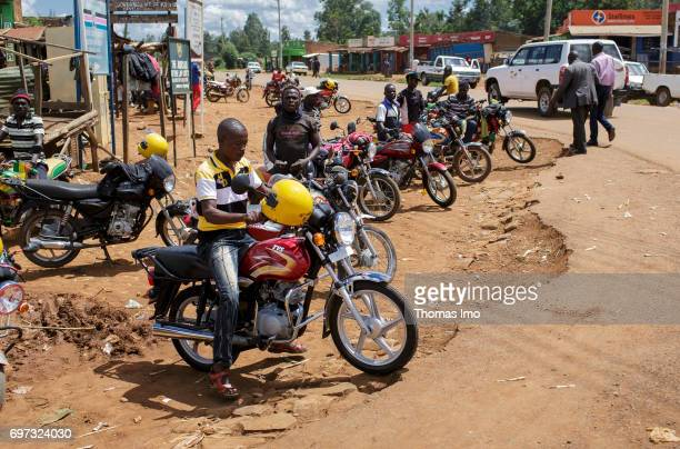 A group of young Africans stands with their motorcycles on a place in Kakamega on May 16 2017 in Kakamega County Kenya