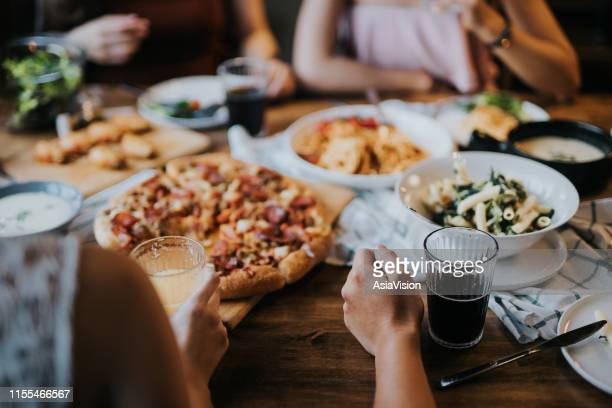 group of young asian man and woman having fun and enjoying food and drinks together during party - dining stock pictures, royalty-free photos & images