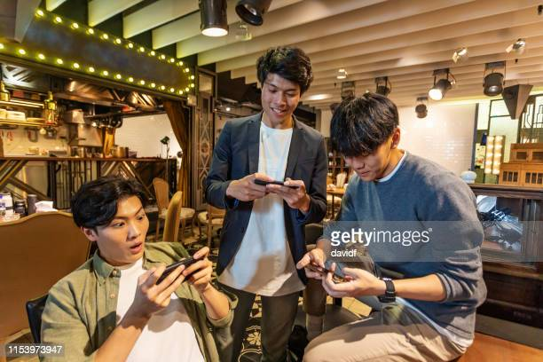 group of young asian men playing video games on their phones - handheld video game stock pictures, royalty-free photos & images