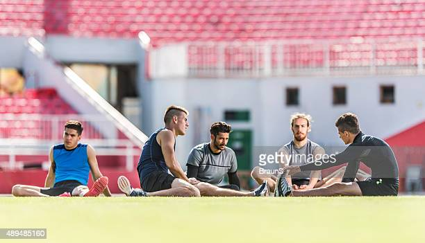 Group of young athletes doing relaxation exercises on grass.