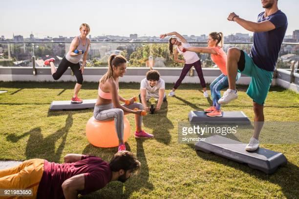 Gruppe junger Sportler mit Sport Training auf einer Penthouse-Terrasse.