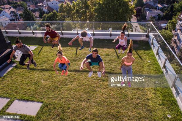 Groep van jonge atleten springen hoog in de lucht tijdens de sport opleiding op een terras.