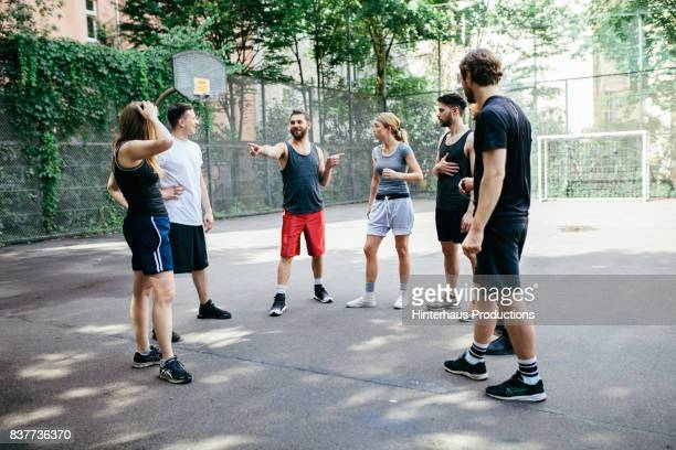 group of young athletes picking sides before friendly outdoor basketball match - seulement des adultes photos et images de collection