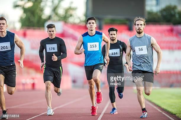 group of young athletic men having a sports race. - vijf personen stockfoto's en -beelden