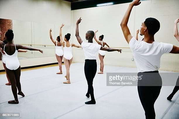 Group of young ballet dancers practicing in studio