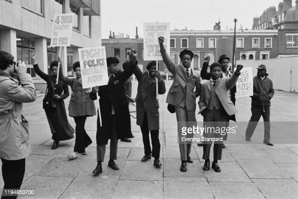 A group of young black men and women hold placards during a demonstation in protest against police brutality aimed at the black community outside the...