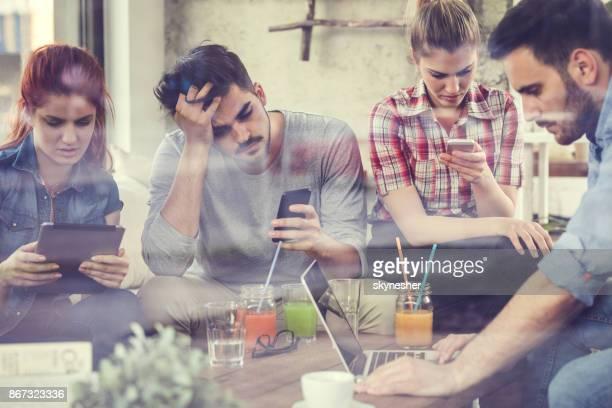 Groupe de jeunes gens s'ennuient à l'aide de la technologie sans fil dans un café.