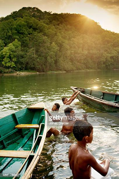 A group of young boy play around floating boats near the lakeside Phewa Lake is a freshwater lake in Nepal located in the south of the Pokhara Valley...