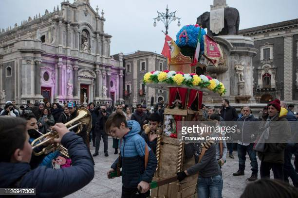 A group of young boys carries a miniature of a so called 'candelora' in front of the Cathedral and the Fountain of the Elephant during the...