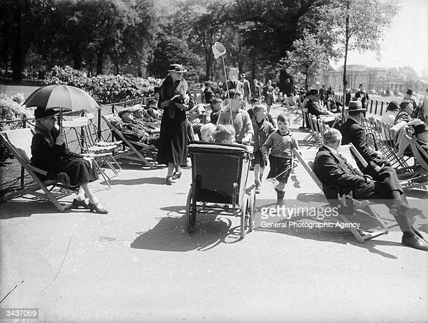 A group of young boys one pushing a pram walk through a crowd sitting in deckchairs enjoying the sun The boys carry fishing nets