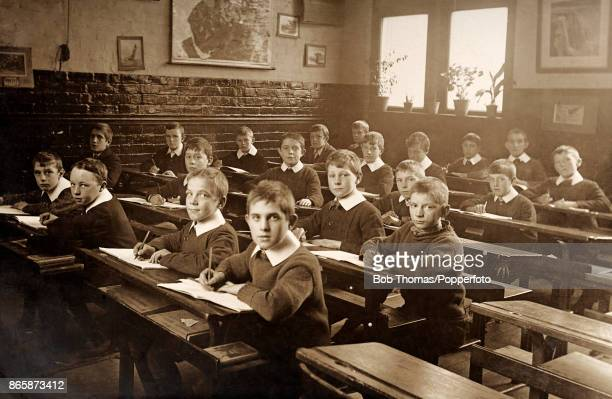 A group of young boys pencils poised over their copy books in a school classroom circa 1910
