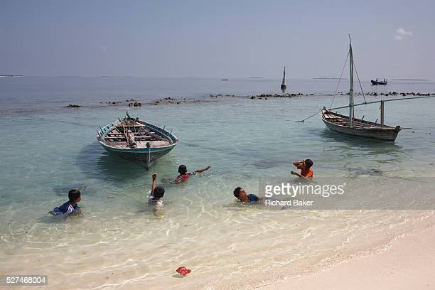 A group of young boys play in the calm waters of the Indian Ocean on Meedu Island in the Republic of the Maldives The shallows are a safe playground...