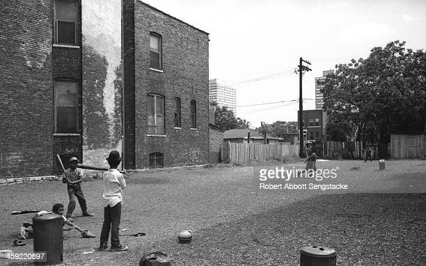 A group of young boys play sandlot baseball in a vacant lot in a Southside Chicago neighborhood late 1960s