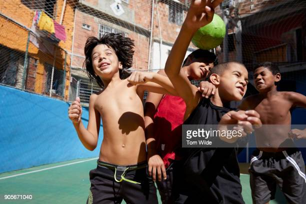 group of young boys playing football outdoors - favela stock pictures, royalty-free photos & images
