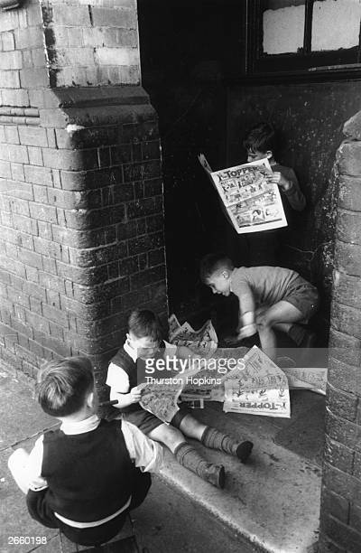 A group of young boys reading a pile of comics Original Publication Picture Post 7230 Children of the Streets pub 1954