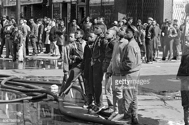 A group of young boys stand in the foreground of a crowd of onlookers who watch firefighters battle a fire after riots erupted in response to the...