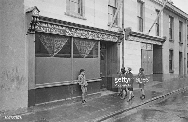 Group of young boys walk past a Zaoula Islamic religious school, located in a converted shop in Tiger Bay, a multicultural area of Cardiff, Wales...