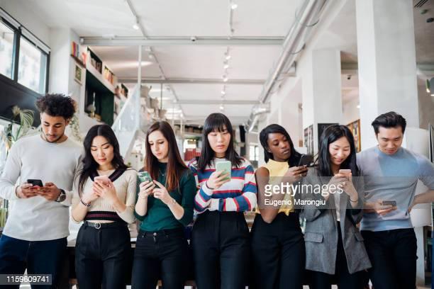 group of young businesswomen and men in a row, looking at smartphones - mittelgroße personengruppe stock-fotos und bilder