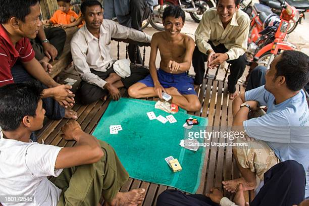 CONTENT] A group of young Cambodian men playing cards on a wooden platform in a street of Phnom Penh Cambodia