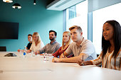 Group Of Young Candidates Sitting At Boardroom Table Listening To Presentation At Business Graduate Recruitment Assessment Day