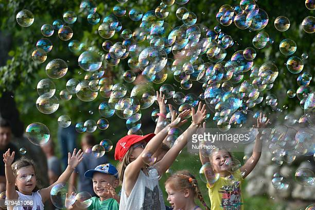 Group of young children enjoys a weekend soap bubbles games near the Wawel Royale Castle in Krakow. On Saturday, 23 July 2016, in Krakow, Poland.