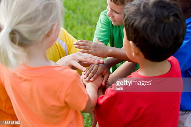 Group of young children, hands in middle showing teamwork