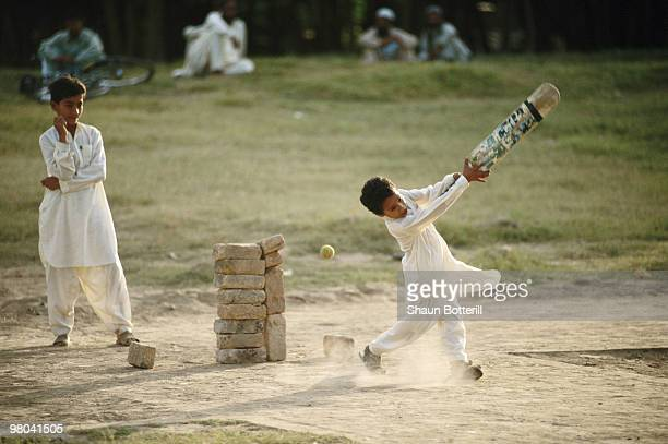 A group of young children use a stack of bricks as a wicket whilst playing cricket on 6 November 1994 in Lahore Pakistan