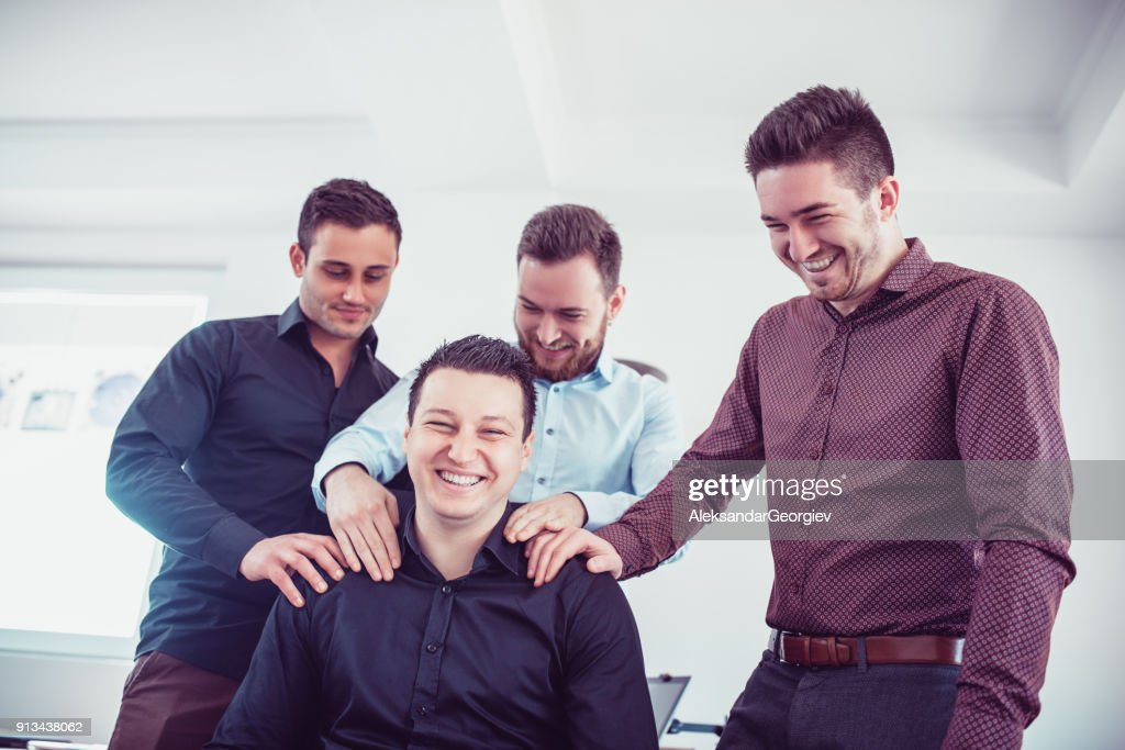 Group of Young Coworkers Making Fun of Colleague in Office : Stock Photo