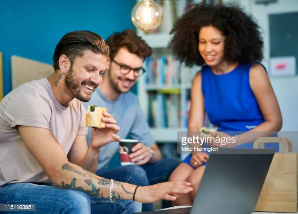 a group of young creative professionals working in a sustainable office environment over lunch. - sleeveless dress stock pictures, royalty-free photos & images