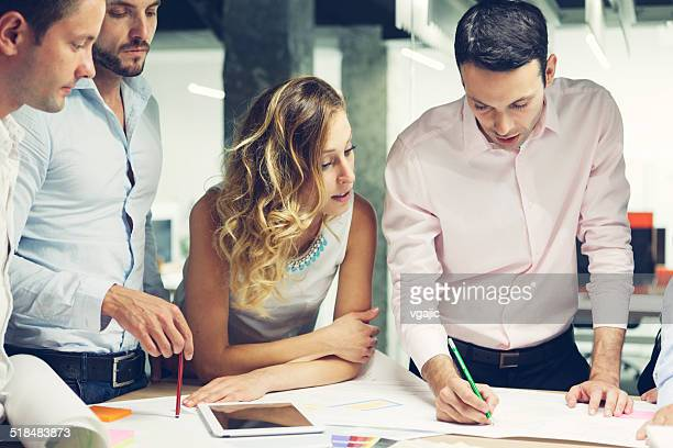 group of young designers reviewing new project in the office. - council flat stock pictures, royalty-free photos & images