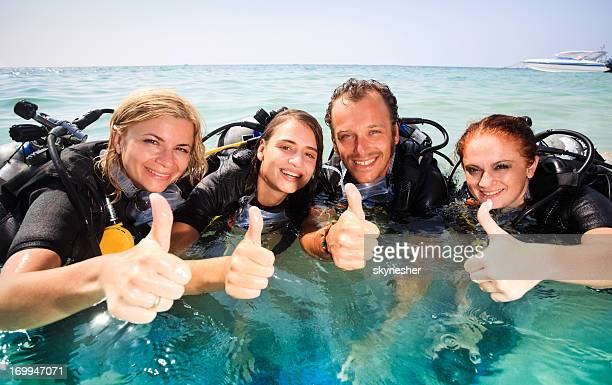 Group of young divers showing ok using their hand gesture.