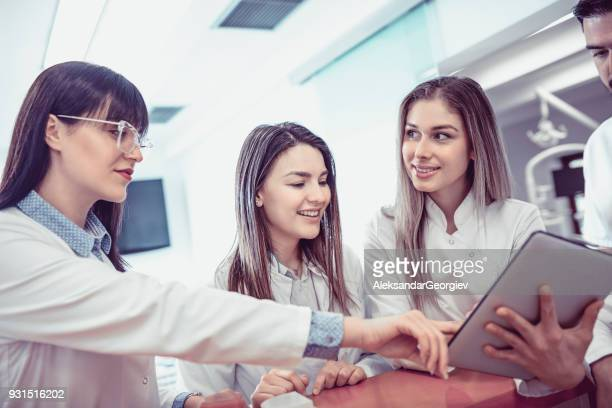 group of young doctors talking at the reception in clinic - medical receptionist uniforms stock photos and pictures