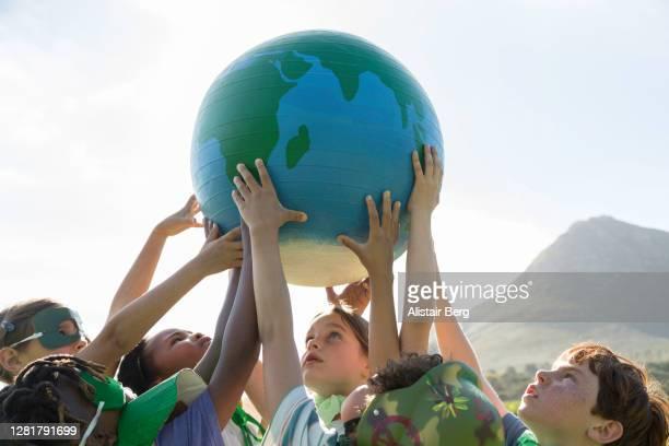 group of young eco-warriors holding up a large globe - rechauffement climatique photos et images de collection