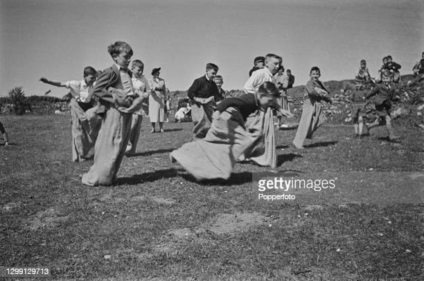 Group of young evacuee schoolboys from Plymouth and London enjoy competing in a sack race during a games class in a field near their allocated...