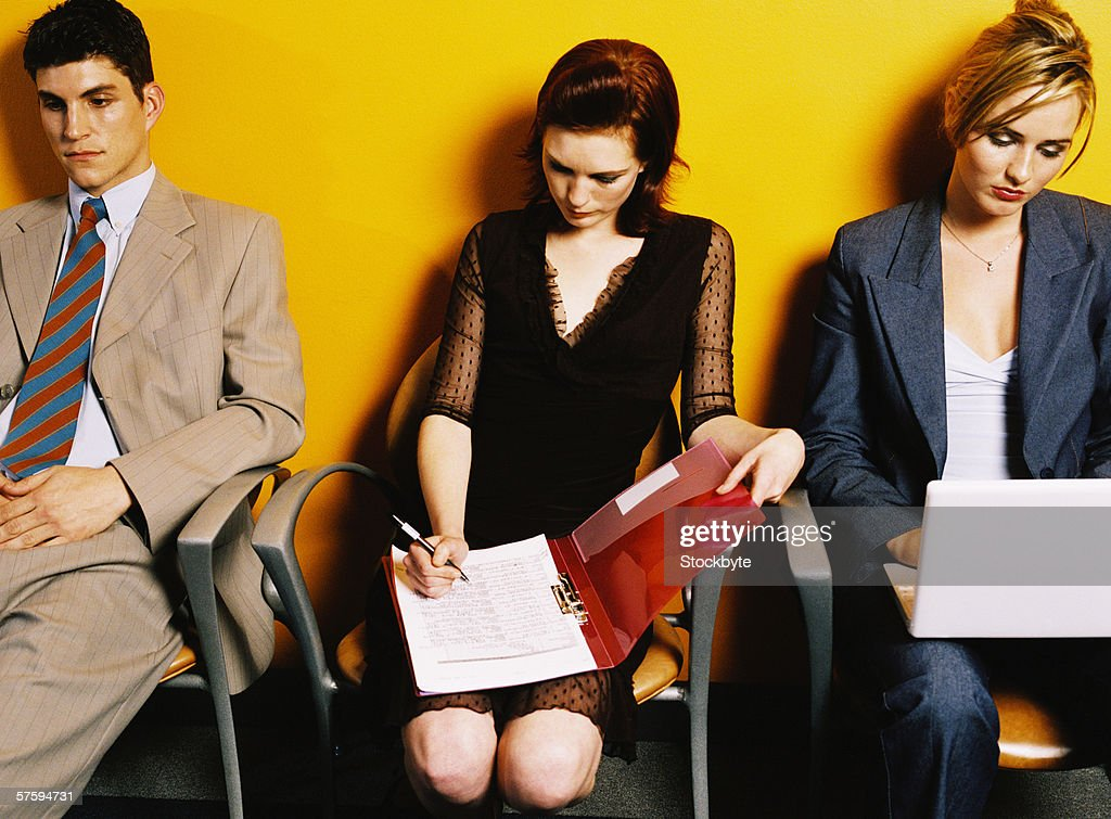 Group of young executives sitting writing notes : Stock Photo