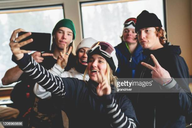 a group of young extreme snowboarders taking selfies after a great day on the slope - winter sports event stock pictures, royalty-free photos & images
