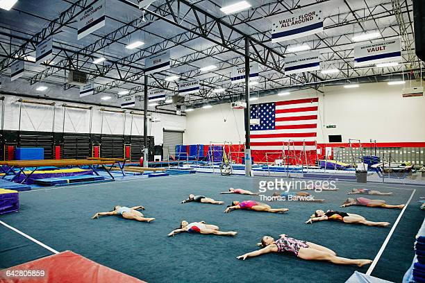 Group of young female gymnasts stretching in gym