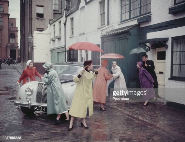 Group of young female models wear raincoats, hats and umbrellas in a variety of pastel shades to protect them from a shower of rain in a mews street...