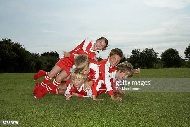 group of young footballers playing - tackling stock pictures, royalty-free photos & images