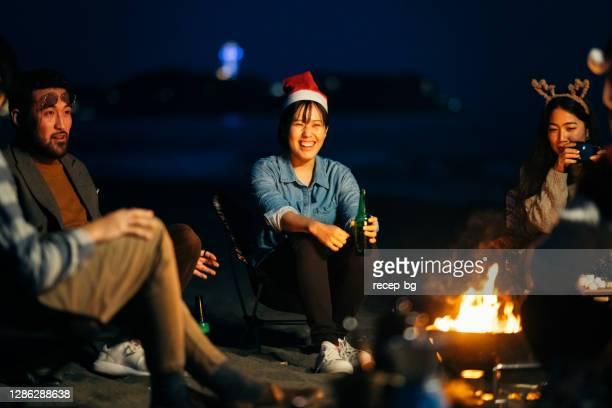 夜にビーチでクリスマスを祝う若い友人のグループ - 焚き火 ストックフォトと画像