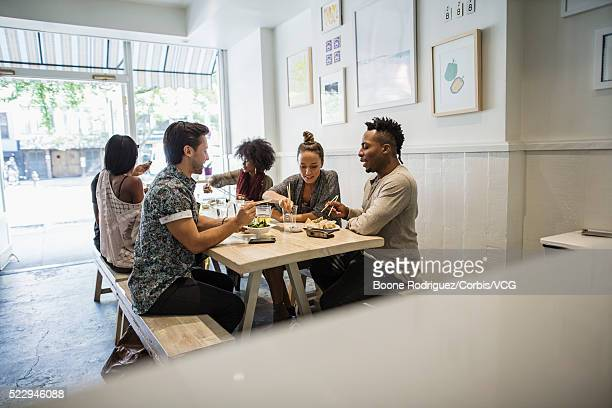 Group of young friends dining together at table