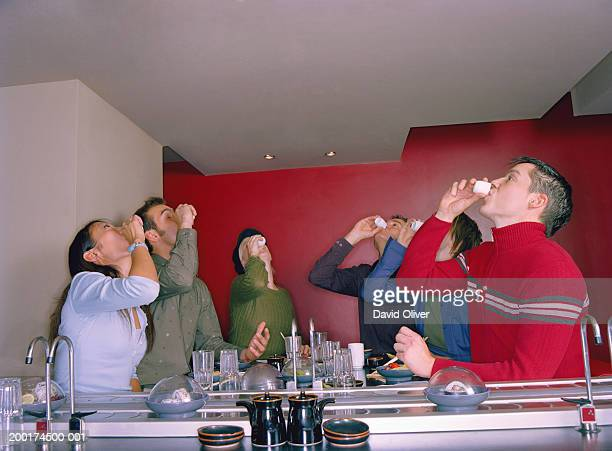 Group of young friends drinking in sushi restaurant