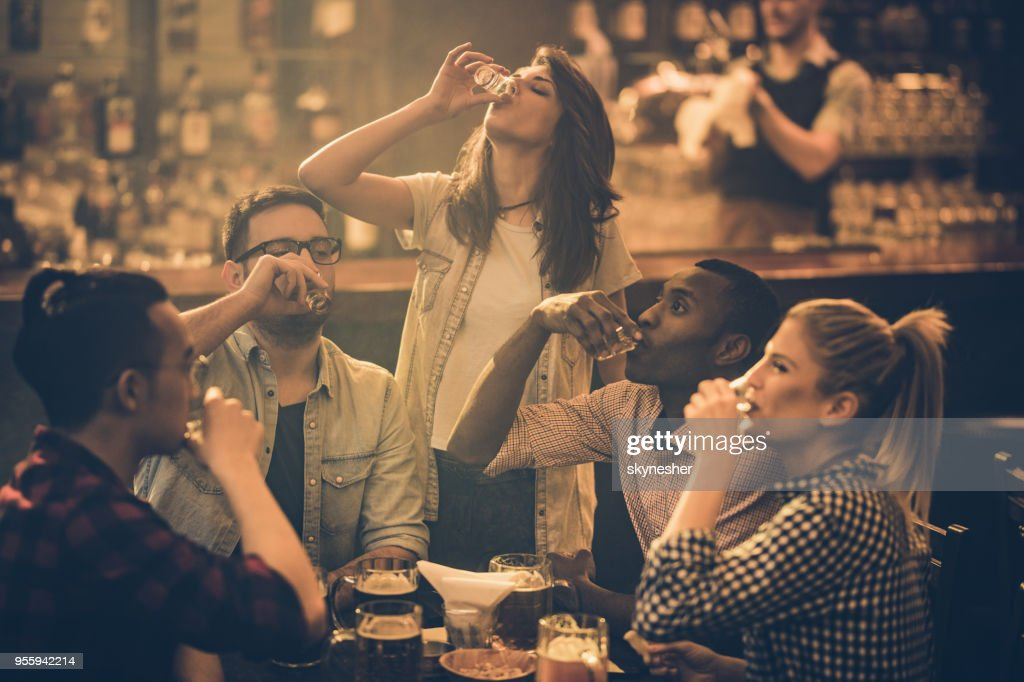 Group of young friends drinking tequila shots in a bar. : Stock Photo