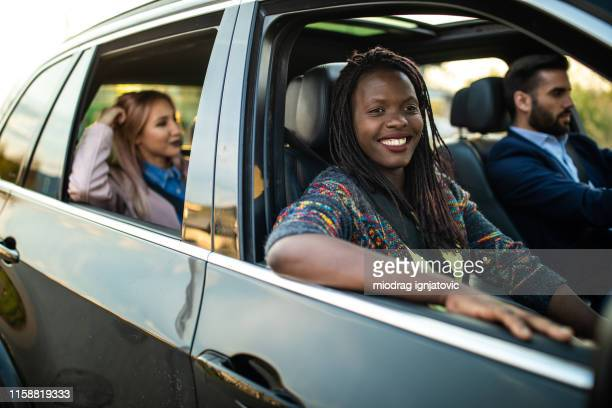 group of young friends driving in a car - car pooling stock photos and pictures