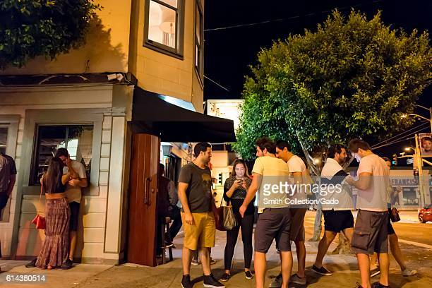 A group of young friends gather and use their cellphones in front of a bar while a couple kisses to the left of the frame in the Cow Hollow...