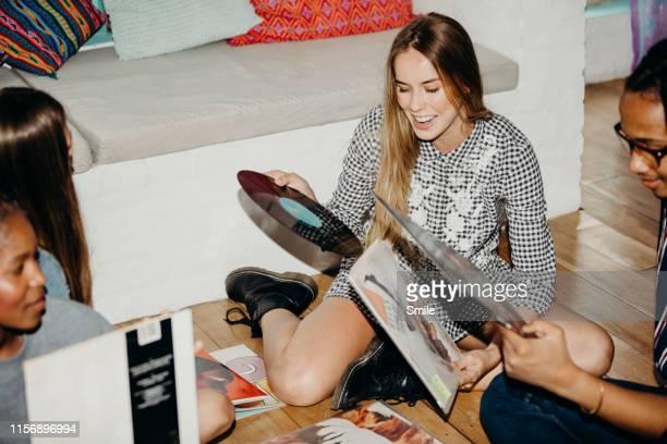 group of young friends going through vinyls - freizeitaktivität stock-fotos und bilder