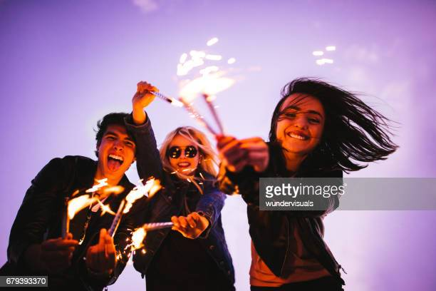Group of young friends having fun with fireworks outdoors