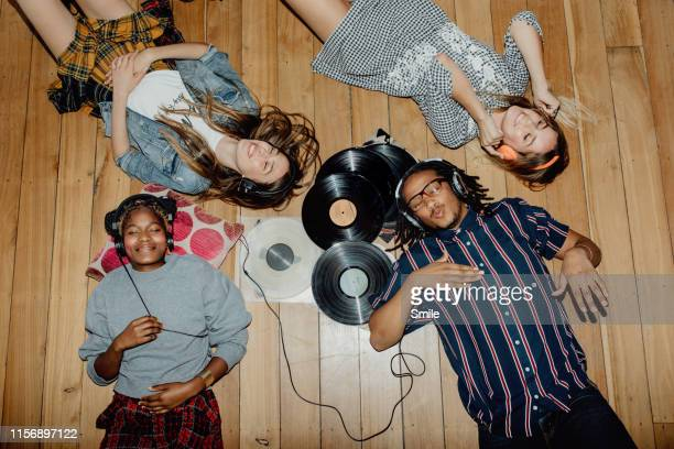 group of young friends listening to music with vinyls scattered about - music stock-fotos und bilder