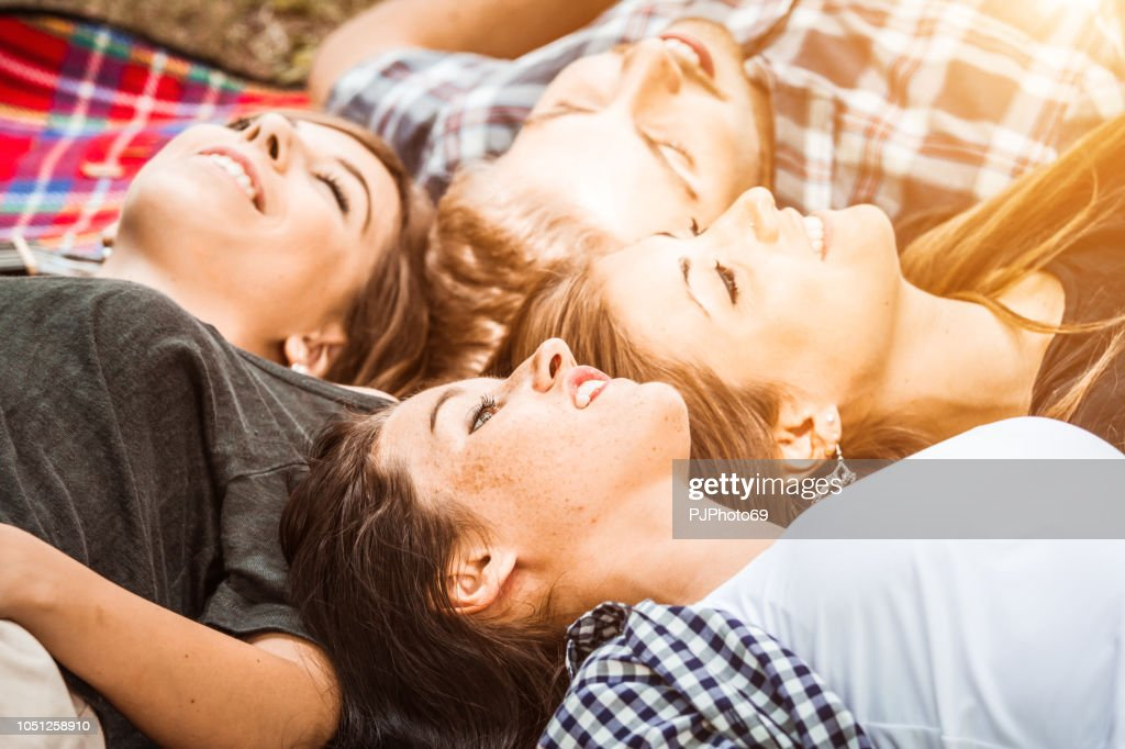 Group of young friends lying down on plaid outdoor looking the sky : Foto stock
